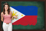 Beautiful and smiling woman showing flag of Philippines on black
