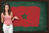 Beautiful and smiling woman showing flag of Morocco on blackboar