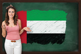 Beautiful and smiling woman showing flag of United Arab Emirates
