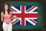 Beautiful and smiling woman showing flag of United Kingdom on bl