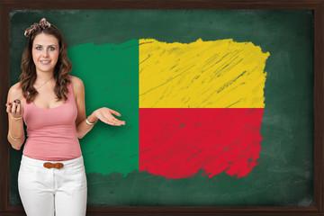 Beautiful and smiling woman showing flag of Benin on blackboard