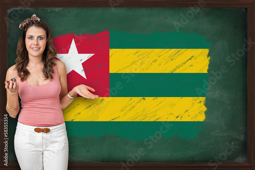 Beautiful and smiling woman showing flag of Togo on blackboard