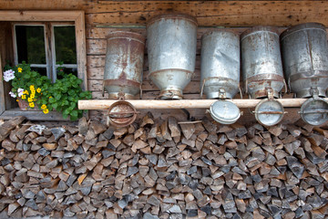 old milk cans on a shelve at a alpine hut