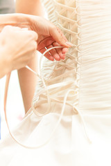 Closeup photo of hands tying ribbon on brides corset