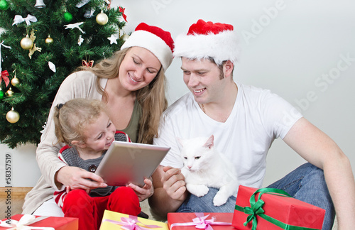 Family with tablet pc in front of christmas tree.