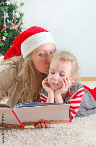 Little girl and her mom reading book at Christmas