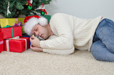 Drunk man with bottle sleeps under christmas tree