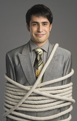 Portrait of a businessman tied up with ropes