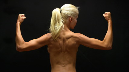 Rear view of blonde woman flexing back muscles