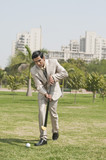 Businessman playing hockey in a park