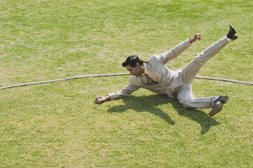 Businessman diving to stop a ball near boundary line in a cricket field