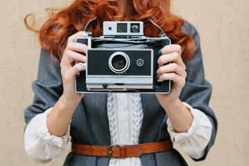 Retro photo camera woman with red hair