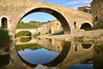 Medieval bridge and houses in Lagrasse, and reflection in the wa