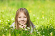 Cute smiling little girl hiding in the grass on the summer field