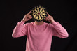 Portrait of teenager holding a dartboard over his face