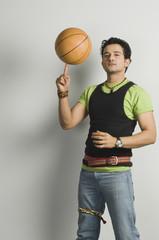 Portrait of a man balancing a basketball on fingertip