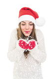 Happy beautiful Santa girl holding and blowing snow