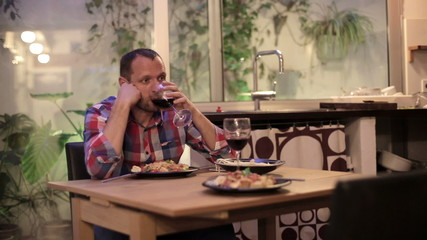 Worried young man drinking red wine and waiting with the dinner
