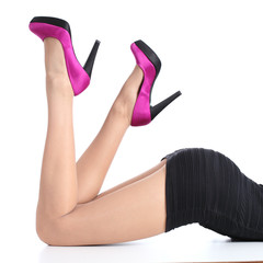 Beautiful woman legs with fuchsia high heels lying down