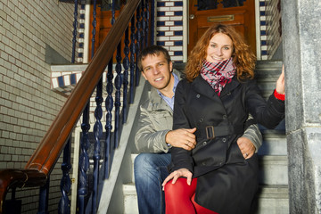 Young couple sitting on a Dutch porch outdoors in autumn.