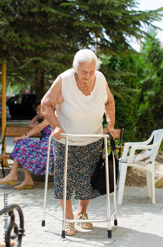 elderly woman standing with her walker