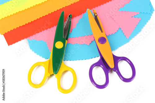 Colorful zigzag scissors with color paper isolated on white