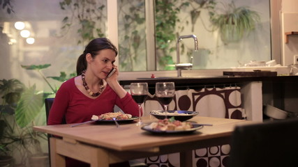 Angry, unhappy woman talking on cellphone, waiting  with dinner
