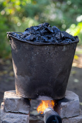 a bucket of tar on the fire, for roof repairs