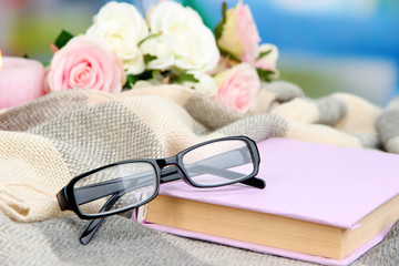 Composition with old book, eye glasses and plaid