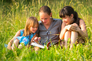 Three cute little girls reading book.