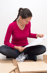 Woman looking at instructions on how to assemble furniture