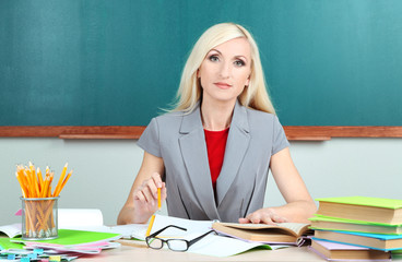 School teacher verifies homework on blackboard background