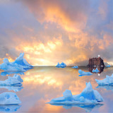 Icebergs floating in the sea at sunset.