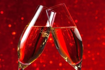 detail of two champagne flutes on red light bokeh background