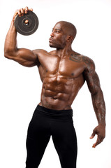 Black bodybuilder training with round discs