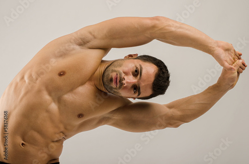 Strong bodybuilder training his six pack. Man doing abs