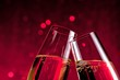 detail of champagne flutes on red light bokeh background