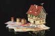 Immobilie mit Eurostücken und Euroscheinen