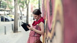 Young trendy woman with tablet computer stand by graffiti wall