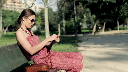 Young woman browsing net on tablet computer in the park