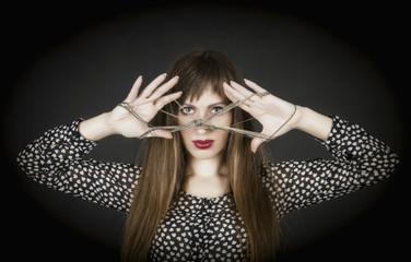 Женщина смотрит через серебряную цепочку.