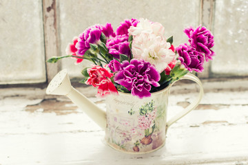 Fresh carnations in watering can  on wooden background