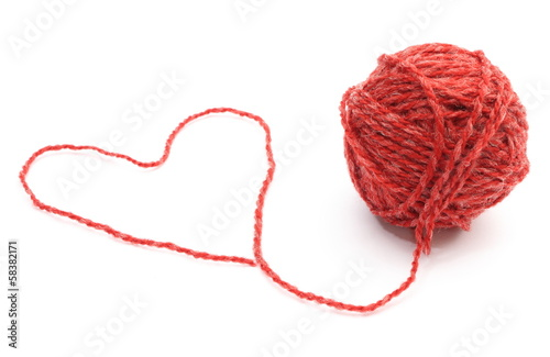 Heart shape and wool ball on white background