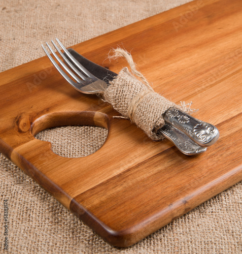 Antique cutlery wrapped in hessian on acacia wood chopping board