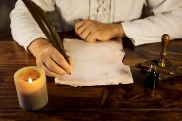mann schreibt auf einem pergament