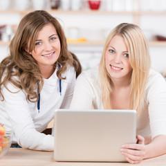 zwei teenager in der küche mit laptop