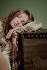 A beautiful teenage girl sleeping on a sound device