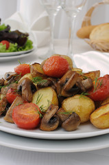 Fried potatoes with mushrooms and tomato
