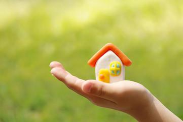 子供の手と家