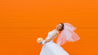 Beautiful bride on orange background on the wedding day